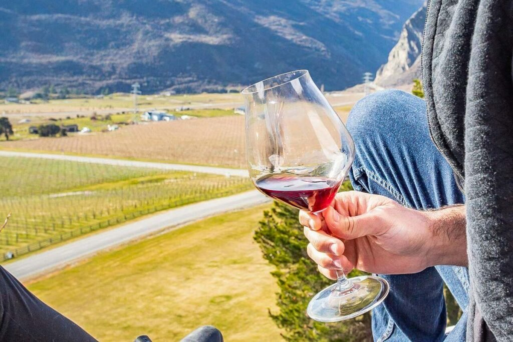 A glass of wine with views over Mt Rosa Winery near Queenstown