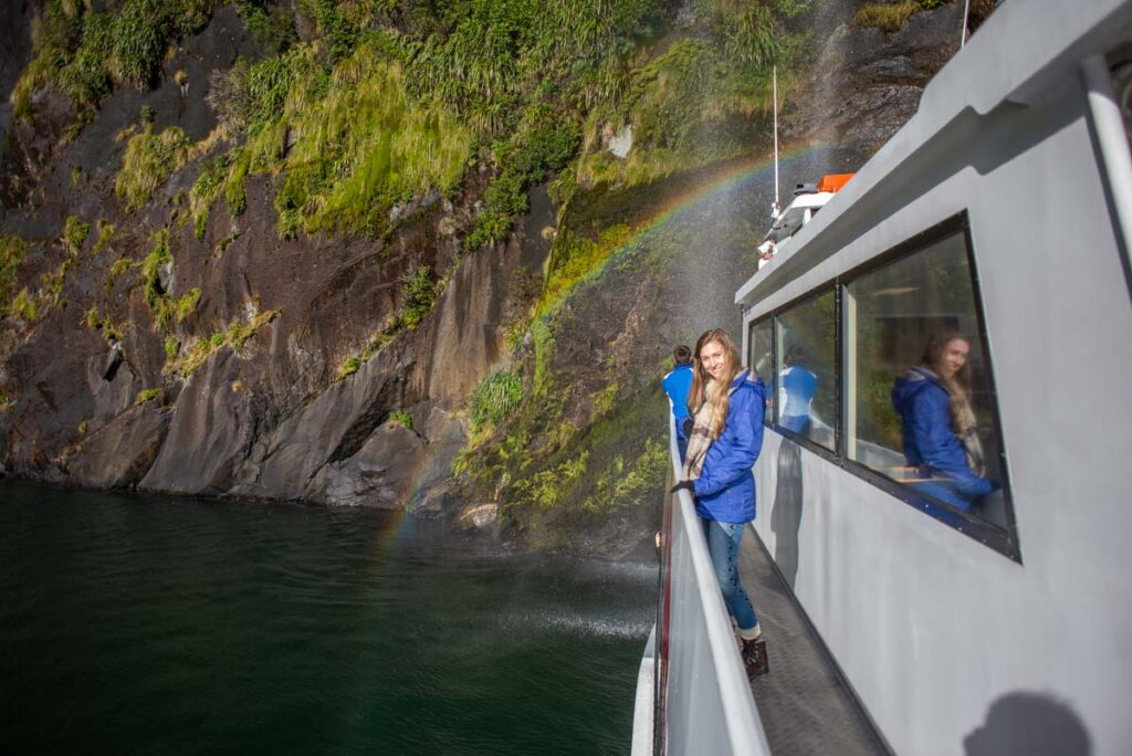 A lady stands on the side of a boat by a waterfall on a cruise through Milford Sound
