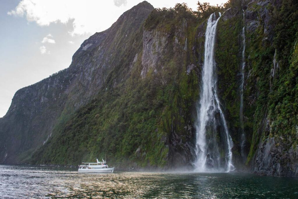 A cruise in Milford Sound approaches a waterfall