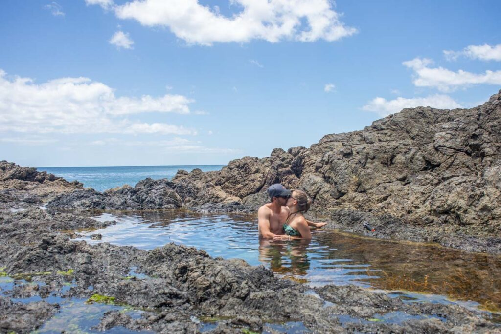 A couple kiss at Mermaid Pools in Northland, NZ