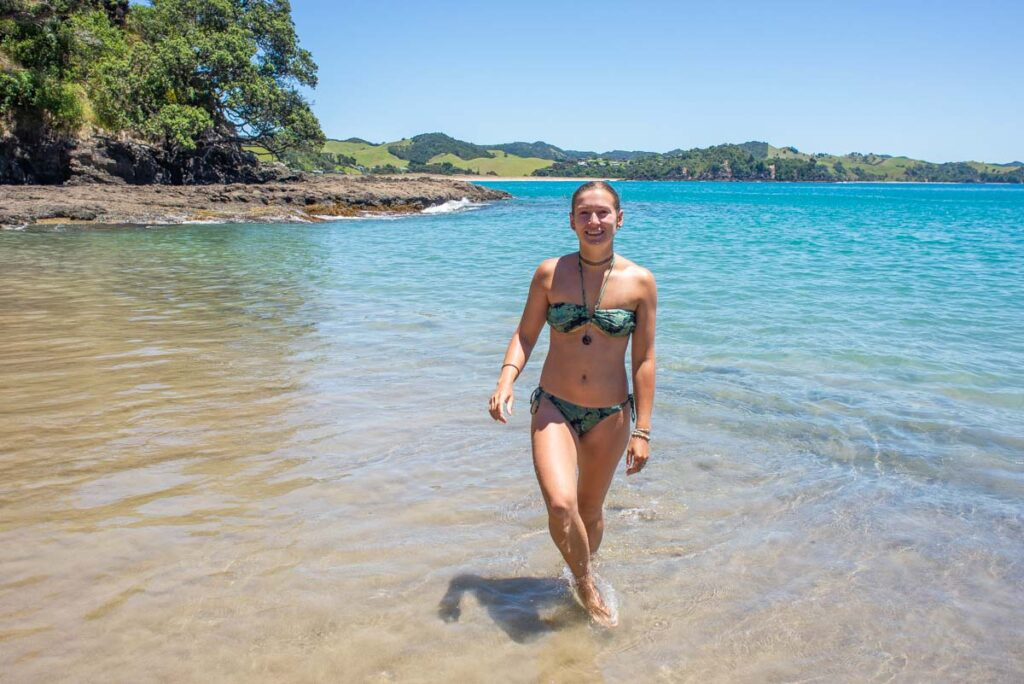 A lady walks out of the ocean at a stunning beach in the Bay of Islands, NZ