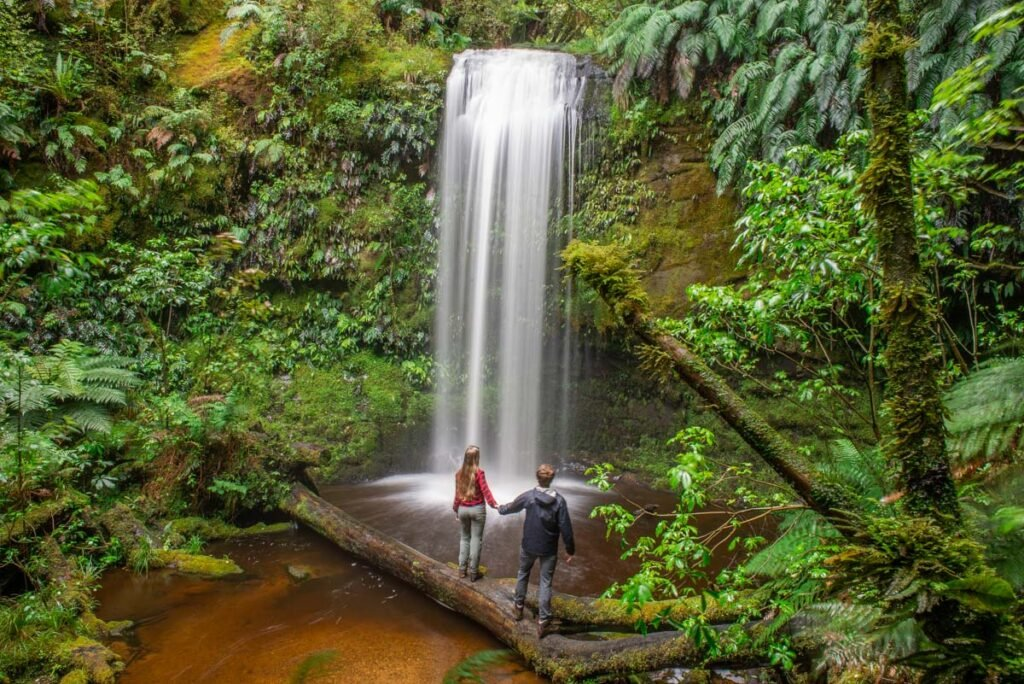 A couple take a photo together at Koropuku Falls in the Catlins region on the South Island of New Zealand