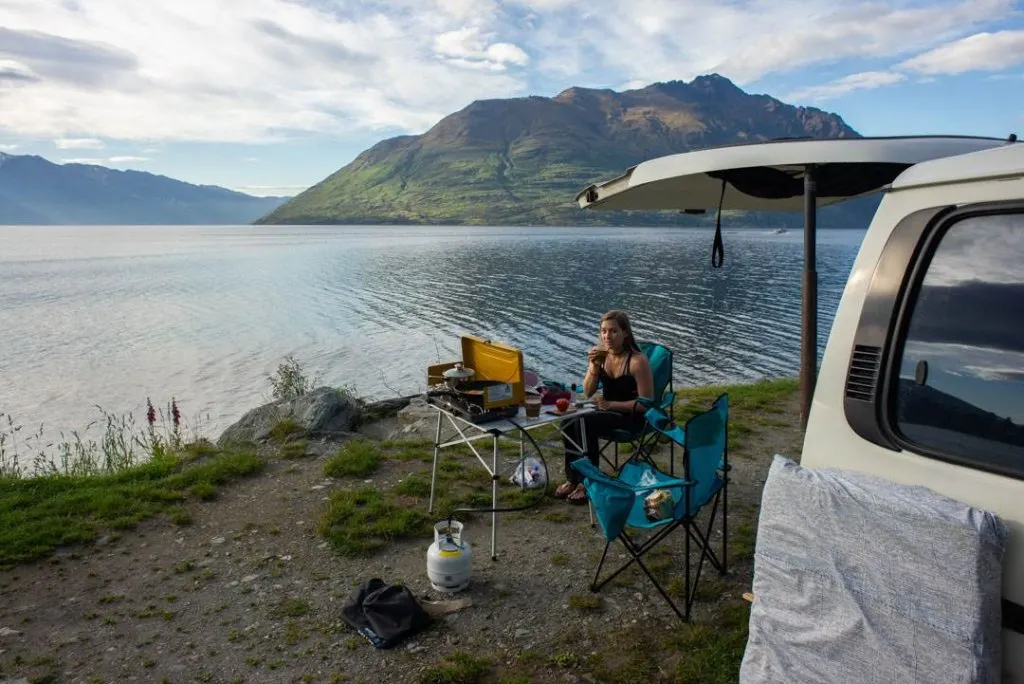 woman freedom camping in a campervan in Queenstown, New Zealand