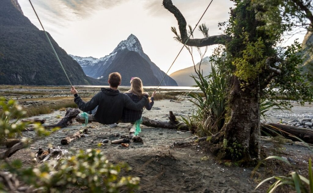 a couple sitting on the Milford Sound Swing