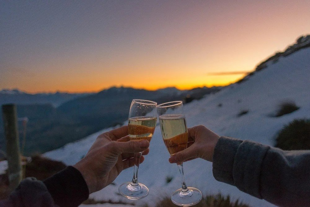 two people cheers champagne with mountain views in New Zeaand