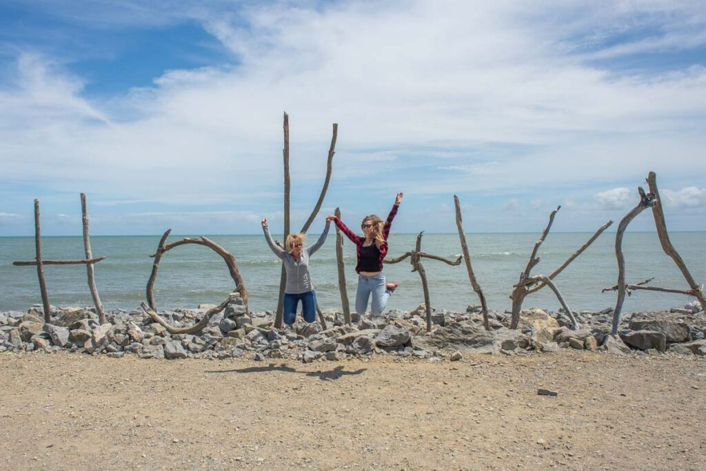 Two people jump in front of the Hokitika sign
