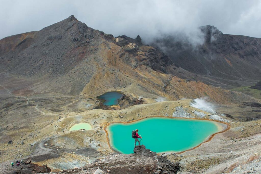 A lady stands above a volcanic lake on the Tongariro Alpine Crossing