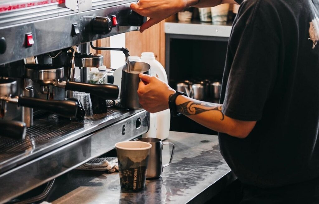 a barista making coffe at the Greedy Cow Cafe in Lake Tekapo